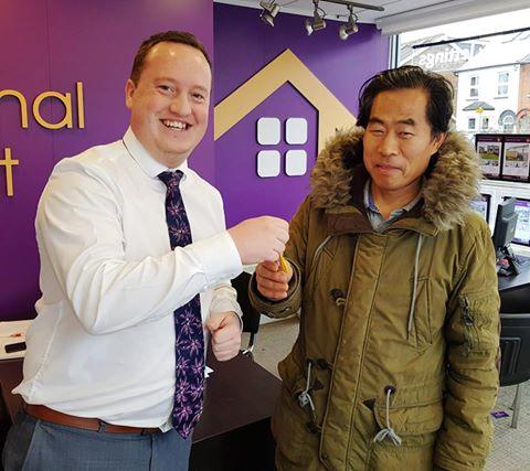 Estate agent handing over keys to new homeowner